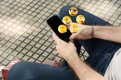 使用智能手机的人送emojis 库存照片