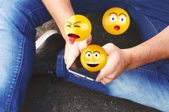 使用智能手机的人送emojis 库存图片