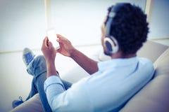 使用智能手机的人,当听到音乐时 免版税库存图片