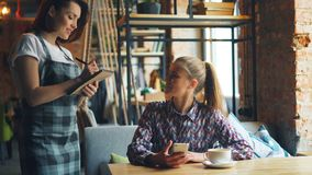 使用智能手机的俏丽的女孩在咖啡厅预定从友好的女服务员 股票视频