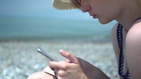 使用智能手机的俏丽的年轻女人由海海滩 减速火箭的帽子和泳装的女孩有蓝色和白色条纹的 股票视频