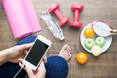 使用智能手机的健康妇女在锻炼和瑜伽、运动器材、水和果子前 图库摄影