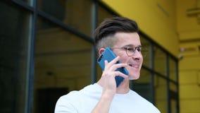 使用智能手机的偶然年轻人 人接近的画象谈话在智能手机微笑的愉快的佩带的白色T恤 股票视频