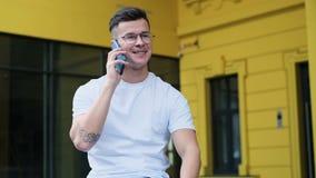 使用智能手机的偶然年轻人 人画象谈话在智能手机微笑的愉快的佩带的白色T恤和眼睛 股票视频
