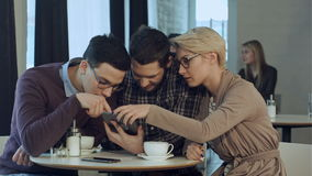 使用智能手机的创造性的队和谈话在偶然办公室 股票录像