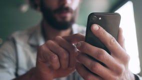 使用智能手机的博客作者的中央部位在咖啡馆 股票录像