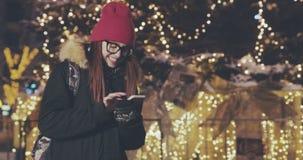 使用智能手机的可爱和快乐的年轻女人在一条拥挤街道 影视素材