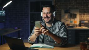 使用智能手机的可爱的人和听到音乐在办公室在晚上 股票录像