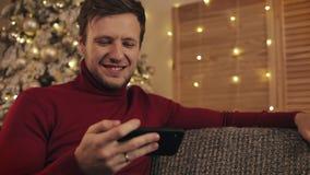 使用智能手机的可爱的人坐长沙发,传讯,微笑在装饰的公寓在好附近 他观看的录影 影视素材