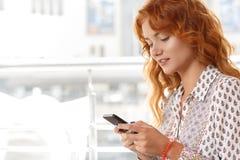 使用智能手机的可爱的女孩在咖啡馆 库存照片