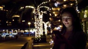 使用智能手机的可爱的妇女在晚上 影视素材