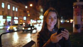 使用智能手机的可爱的妇女,当走通过平衡的城市的街道时 影视素材