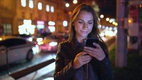 使用智能手机的可爱的妇女,当走通过平衡的城市的街道时 股票录像