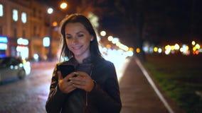 使用智能手机的可爱的妇女,当走通过平衡的城市的街道时 股票视频