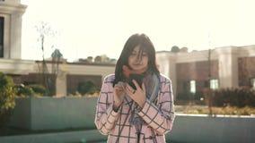 使用智能手机的可爱的少妇在城市,穿戴在外套和帽子 少妇在读一则消息 影视素材