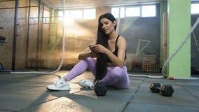 使用智能手机的可爱的适合的妇女,当休息在训练以后在健身房时 股票录像