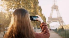 使用智能手机的后面观点的年轻少年女性对为埃佛尔铁塔照相在巴黎,法国 影视素材