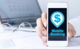 使用智能手机的商人为流动银行业务 库存图片