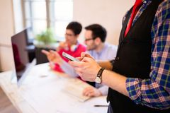 使用智能手机的商人在现代办公室,特写镜头 库存照片