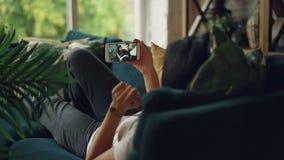使用智能手机的善社交的女孩背面图打说谎网上录影的电话在长沙发在舒适房子,人们谈话 股票视频