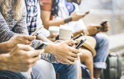 使用智能手机的多文化朋友小组有咖啡杯的 免版税库存图片