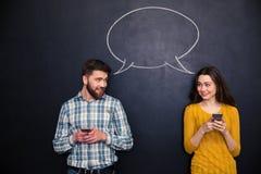 使用智能手机的夫妇在有讲话的黑板对话 免版税图库摄影