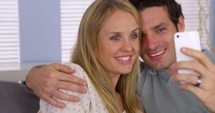使用智能手机的夫妇对与家庭的网络摄影 免版税库存图片