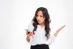 使用智能手机的失望的迷茫的亚裔女实业家 库存图片