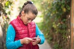 使用智能手机的女孩 免版税图库摄影