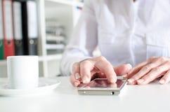 使用智能手机的女实业家在咖啡休息期间 免版税库存照片