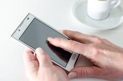 使用智能手机的女实业家在咖啡休息期间 免版税库存图片