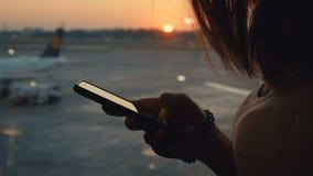 使用智能手机的女性剪影 妇女手接近的射击有机动性的在日落或日出背景在机场 影视素材
