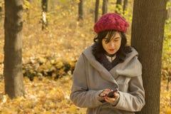 使用智能手机的女性在森林 免版税库存图片