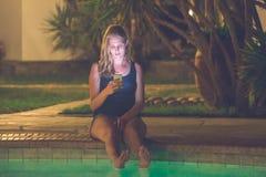 使用智能手机的女性在游泳池边 城市点燃晚上场面 图库摄影