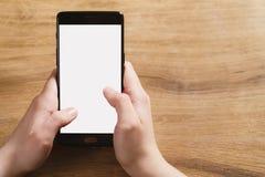 使用智能手机的女性青少年的手有空白的白色屏幕的 免版税库存照片