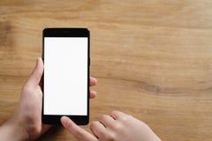 使用智能手机的女性青少年的手有空白的白色屏幕的 免版税图库摄影
