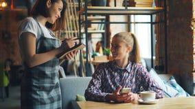 使用智能手机的女性顾客在咖啡馆然后谈话与女服务员微笑 股票视频