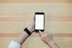 使用智能手机的妇女为在桌上的应用在办公室 免版税库存照片