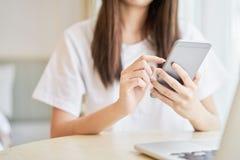 使用智能手机的妇女为在桌上的应用在屋子里 数字技术的概念 免版税库存照片