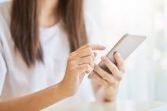 使用智能手机的妇女为在桌上的应用在屋子里 免版税库存照片