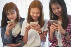 使用智能手机的妇女为在桌上的应用在屋子里 免版税库存图片
