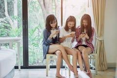 使用智能手机的妇女为在桌上的应用在屋子里 免版税图库摄影