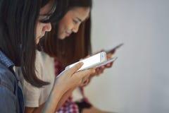 使用智能手机的妇女为在桌上的应用在屋子里 图库摄影