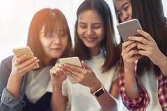 使用智能手机的妇女为在桌上的应用在屋子里 库存照片