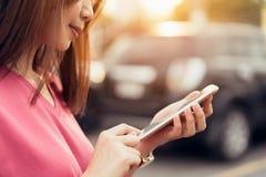 使用智能手机的妇女为在汽车迷离背景的应用 免版税库存照片