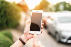 使用智能手机的妇女为在汽车迷离背景的应用 免版税库存图片