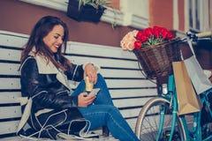 使用智能手机的妇女和喝咖啡在城市街道 库存图片