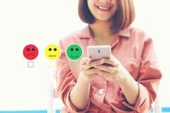 使用智能手机的妇女和投入与兴高采烈的面孔标志的校验标志在咖啡馆、满意评估和顾客 免版税库存图片