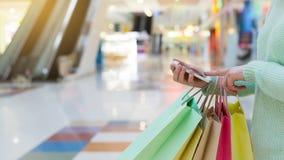 使用智能手机的妇女和拿着购物带来 免版税库存图片