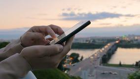 使用智能手机的妇女在城市在日落以后 股票视频